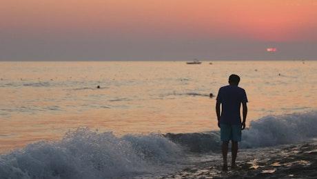 Depressed man in the seashore at sunset