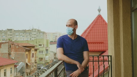 Depressed man stands on balcony in face mask