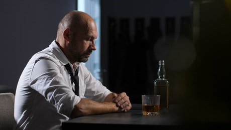 Depressed man with a bottle of whisky