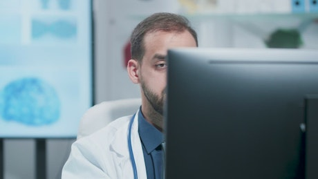 Depressed medical professional working on PC in lab