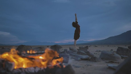 Deserted plain with a campfire and a woman practicing yoga