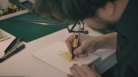 Designer in his studio giving color to his strokes in a notebook