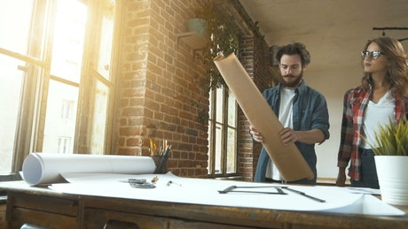 Designers unroll plans onto desk in studio