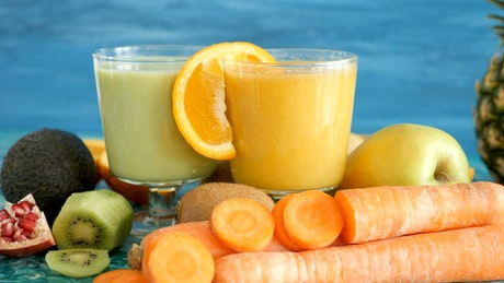 Detox diet smoothies surrounded by fruits and vegetables