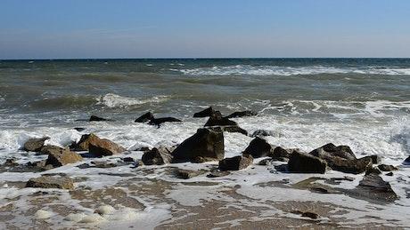 Dirty seawater breaking over rocks