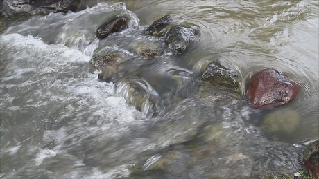 Dirty stream flowing over pebbles
