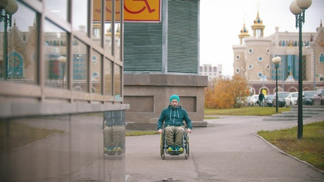 Disabled man in a wheelchair and a disabled sign