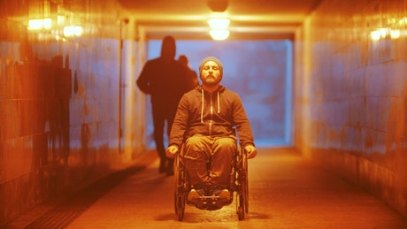 Disabled man in a wheelchair riding in the underpass
