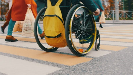 Disabled man on a wheelchair on pedestrian crossing