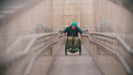 Disabled man struggling to go up the ramp
