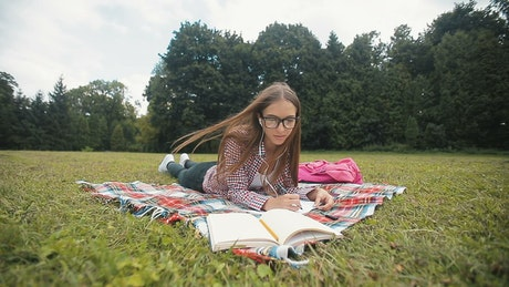 Distance education student listens to lecture in park