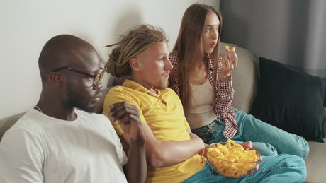 Diverse friends watch movie on sofa with snacks
