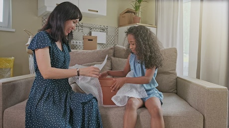 Diverse mom and daughter play on sofa in new home