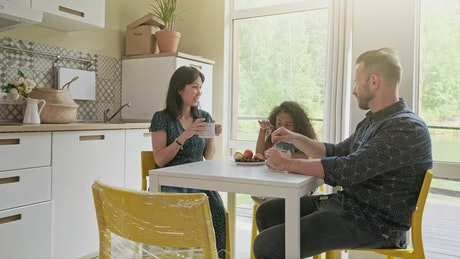 Diverse race family sit at kitchen table drinking coffee