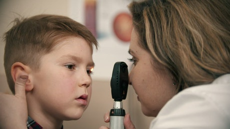 Doctor checking a boy vision with a device