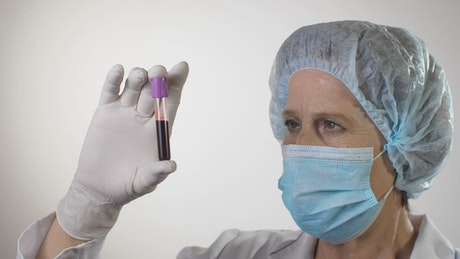 Doctor examining a blood test wearing mask