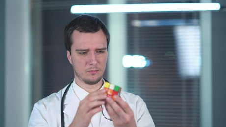Doctor playing with Rubik's cube