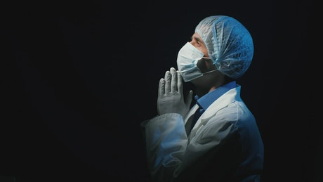 Doctor praying in a dark room looking at sky