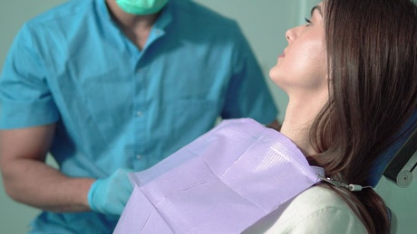 Doctor prepares patient for exam with face mask