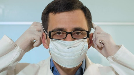 Doctor puts on a mask in the hospital, portrait