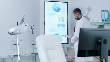 Doctor reviews 3D DNA models on large screen