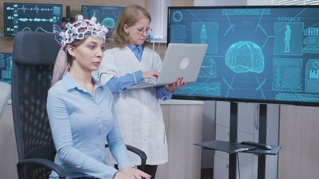 Doctor studies patient brain scan and types on laptop