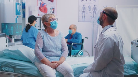 Doctor talking to his patient in hospital