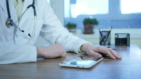 Doctor typing on a tablet in the office