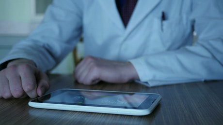 Doctor using a tablet on the desk