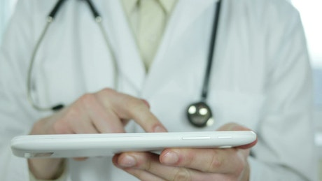 Doctor using the tablet with the fingers