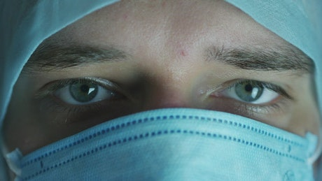 Doctor with a face mask closes his eyes