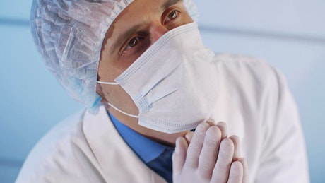 Doctor with face mask praying to heaven