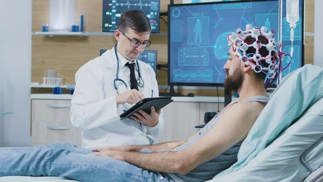 Doctor with patient reviews brain scan on screen