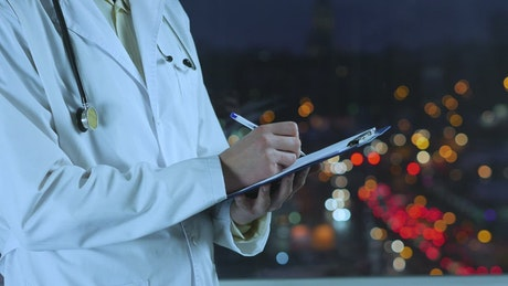 Doctor writing a prescription with an unfocused street background