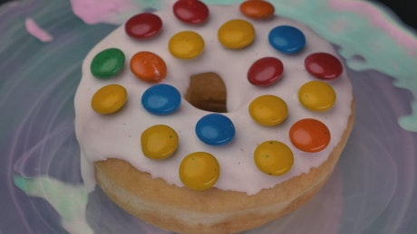 Donut with white frosting and colored chocolates