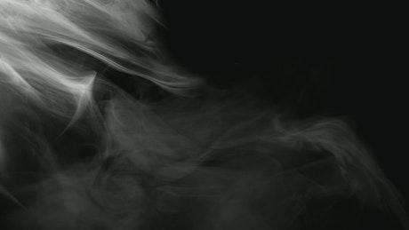 Drafting smoke across a dark screen