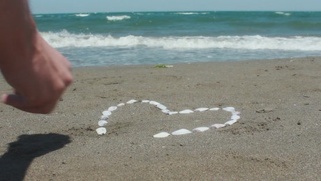 Drawing a heart on the beach using oysters
