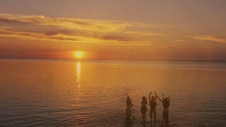 Dreamy sunset view of people jumping on sea surface