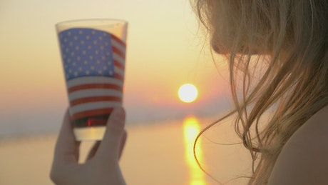 Drinking from a glass with the American flag