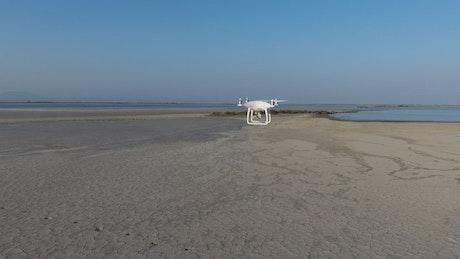 Drone flying above a sandy landscape