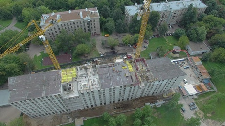 Drone flying above construction cranes