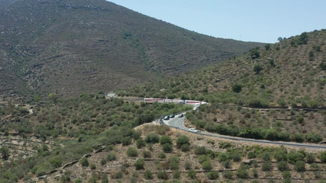 Drone flying along a winding road in the hills