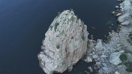 Drone flying over coastal rocks