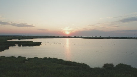 Drone flying over wetlands at sunset