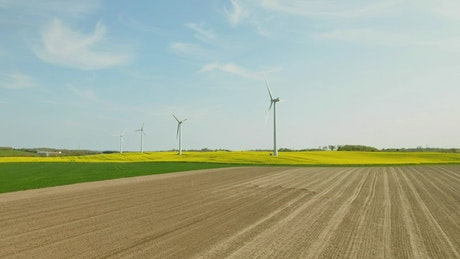 Drone flying past wind turbines