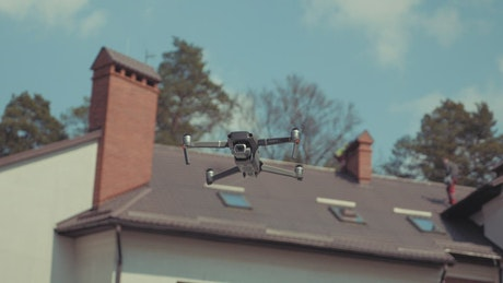 Drone hovering in front of a house