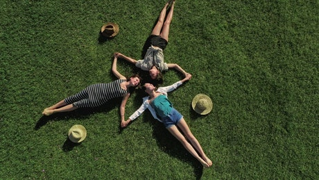 Drone view of girls lying on grass in star pattern