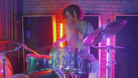 Drummer playing in a studio with neon lights