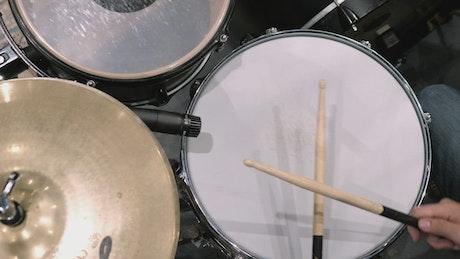 Drummer using drumsticks