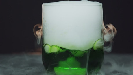 Dry ice in a glass of green liquid